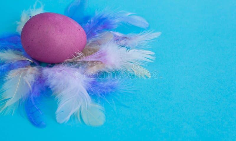 Ovo da páscoa roxo em um fundo azul da cor com um espaço da cópia foto de stock royalty free