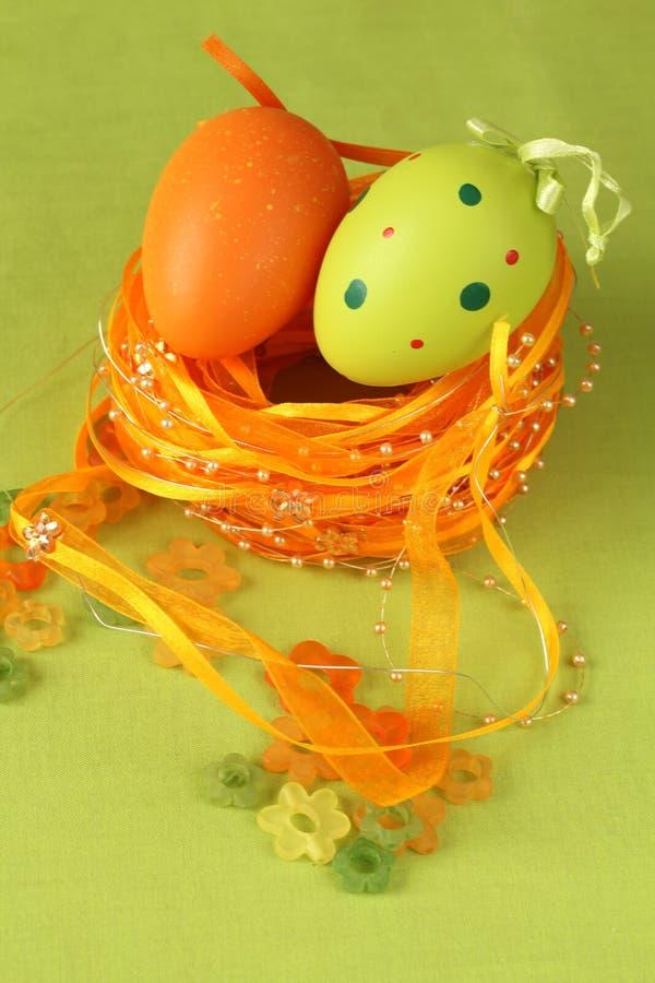 Ovo de Easter verde e alaranjado em um ninho fotografia de stock