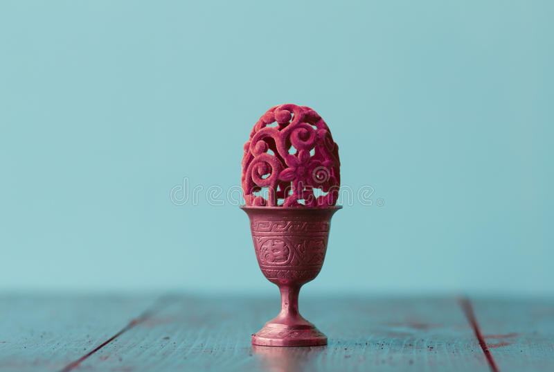 Ovo decorativo da Páscoa bonita em um copo de ovo de bronze imagens de stock