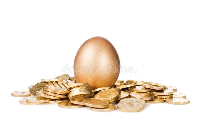 Ovo do ouro em moedas douradas imagens de stock royalty free