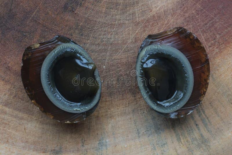 Ovo do século cortado ao meio em uma placa de madeira foto de stock