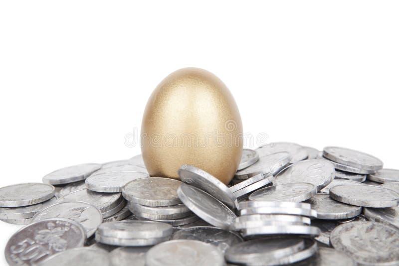 Ovo dourado com moedas imagens de stock royalty free