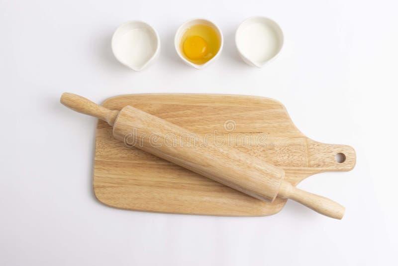 Ovo, farinha, leite, placa de corte, pino do rolo para cozer fotografia de stock