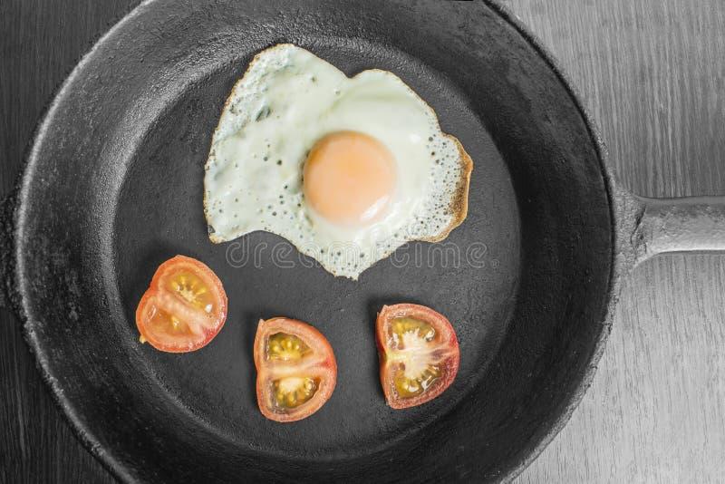 Ovo frito com tomates em uma frigideira do ferro fundido em uma tabela de madeira foto de stock