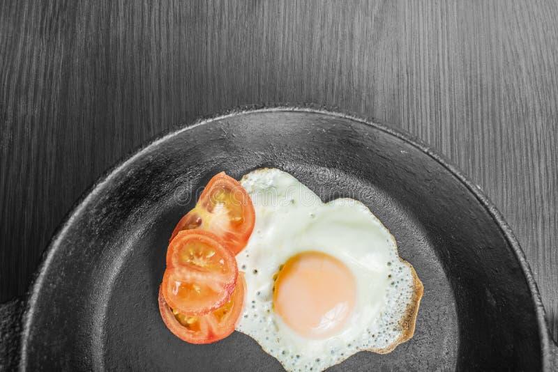 Ovo frito com tomates em uma frigideira do ferro fundido em uma tabela de madeira imagem de stock