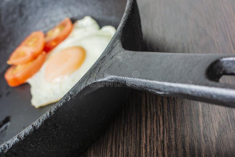 Ovo frito com tomates em uma frigideira do ferro fundido em uma tabela de madeira foto de stock royalty free