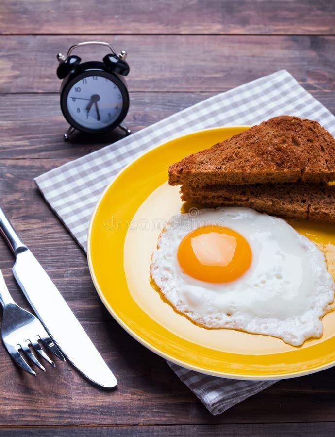 Ovo frito e pão na placa amarela fotografia de stock