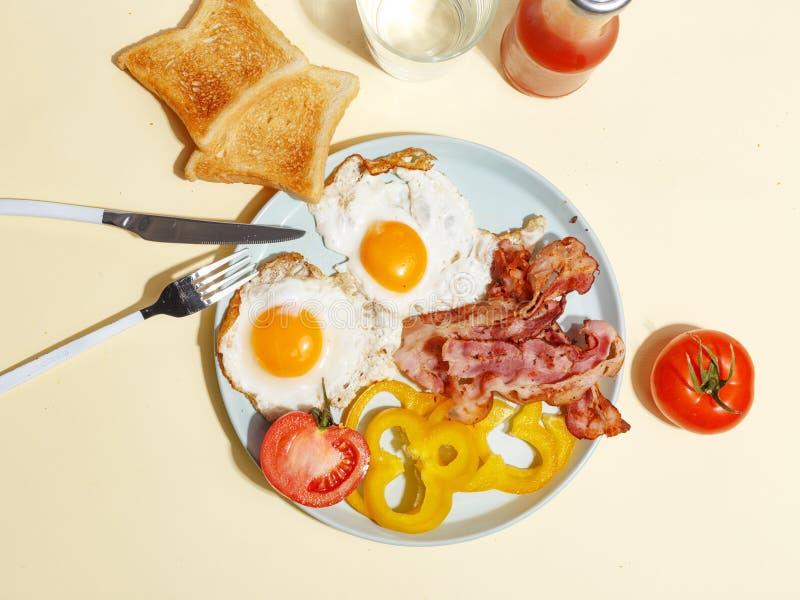 Ovo frito simples do café da manhã com bacon, pimenta de sino e brinde em uma placa fotos de stock royalty free
