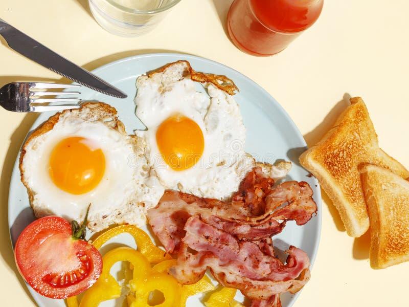 Ovo frito simples do café da manhã com bacon, pimenta de sino e brinde em uma placa imagem de stock royalty free
