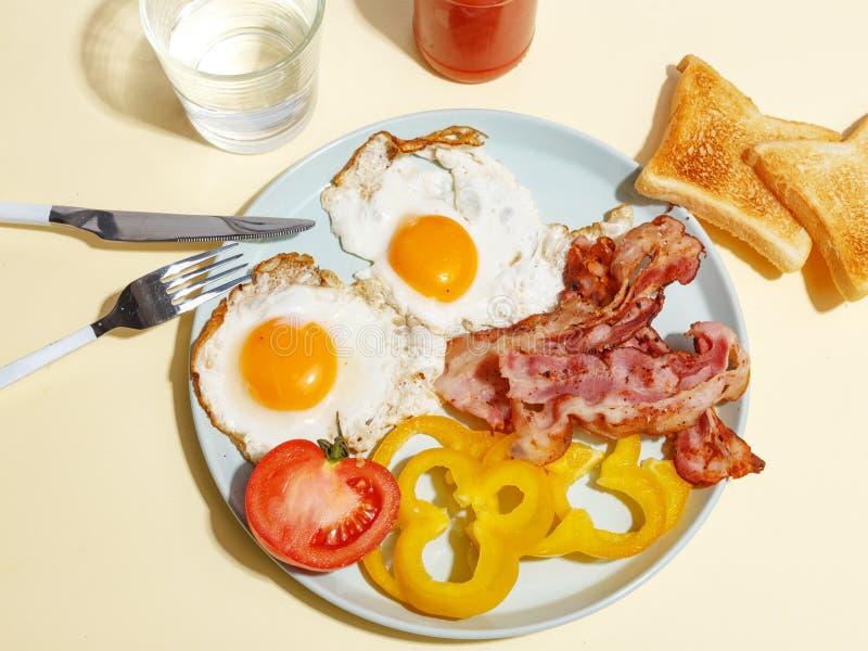 Ovo frito simples do café da manhã com bacon, pimenta de sino e brinde em uma placa imagem de stock
