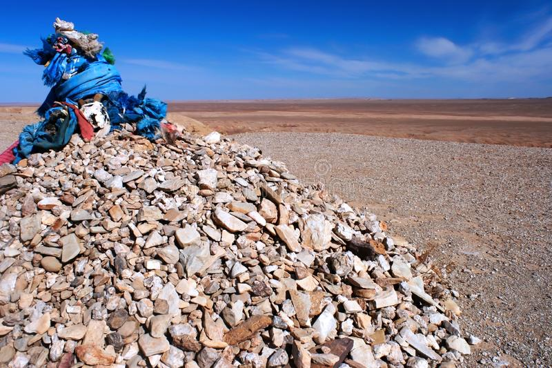 Ovoo, oboo or obo ceremonial rock pile with sacred hadags or khadags blue silk scarves with a goat skull, Gobi Desert Mongolia. Shamanic ovoo, oboo or obo stock images