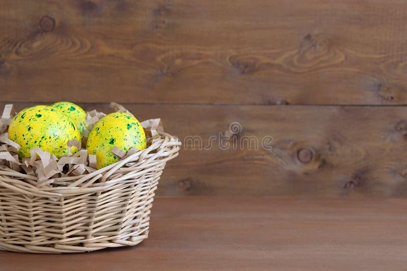 Ovos amarelos da Páscoa na cesta da palha Em um fundo de madeira marrom imagem de stock royalty free