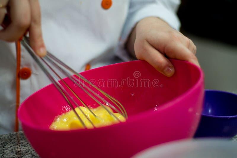 Ovos batendo do cozinheiro chefe da mulher fotos de stock