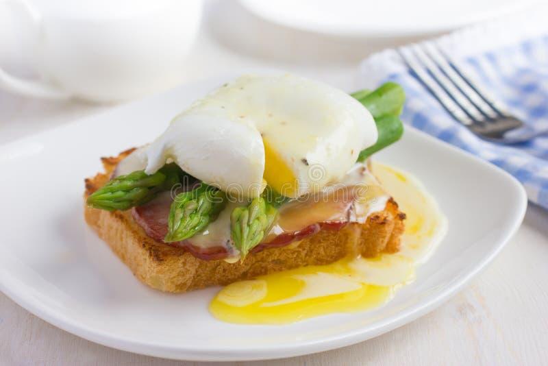 Ovos Benedict com molho do hollandaise no brinde com bacon e como fotografia de stock