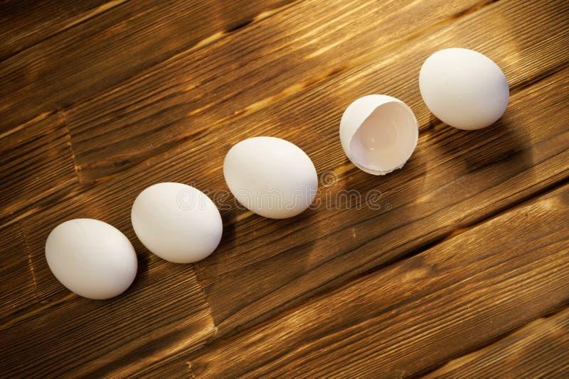 Ovos brancos da galinha em uma tabela de madeira Quebrado e inteiro naughty fotografia de stock