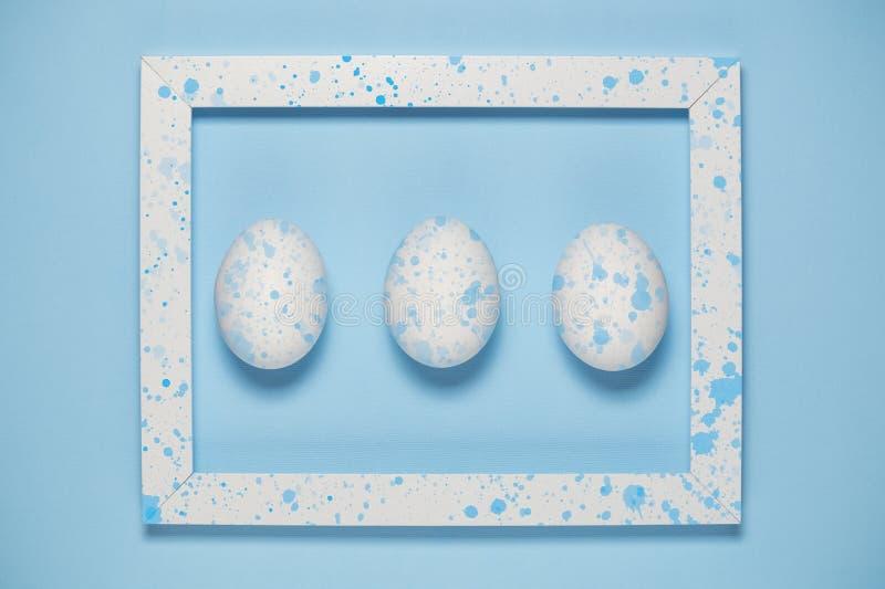 Ovos brancos e quadro artístico no fundo azul liso imagens de stock