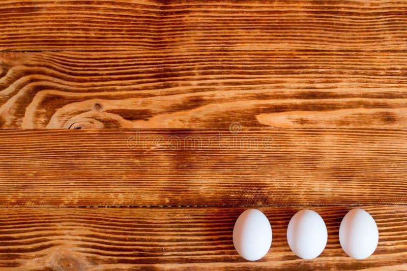 Ovos brancos em um fundo de madeira fotografia de stock royalty free