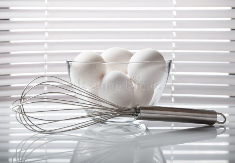Ovos brancos no batedor de ovos da bacia e do fio fotografia de stock