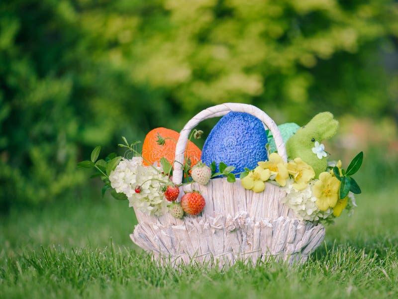 Ovos, coelho, flores e bagas coloridos em cesta ajustada do presente da Páscoa fotografia de stock royalty free