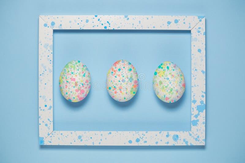 Ovos coloridos e quadro artístico no fundo azul liso imagens de stock