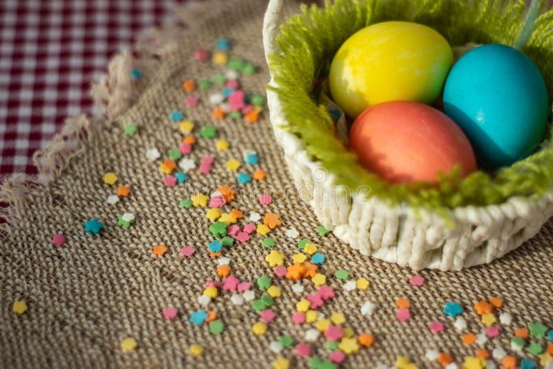 Ovos coloridos na cesta festiva de easter no guardanapo da lona fotos de stock royalty free