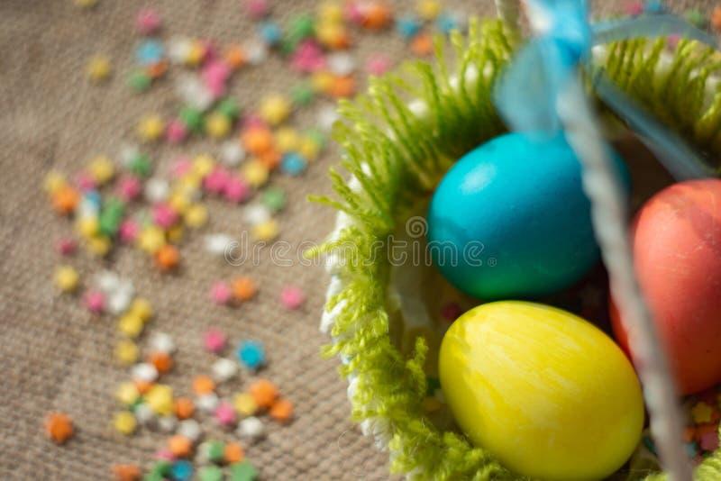 Ovos coloridos na cesta festiva de easter no guardanapo da lona imagens de stock