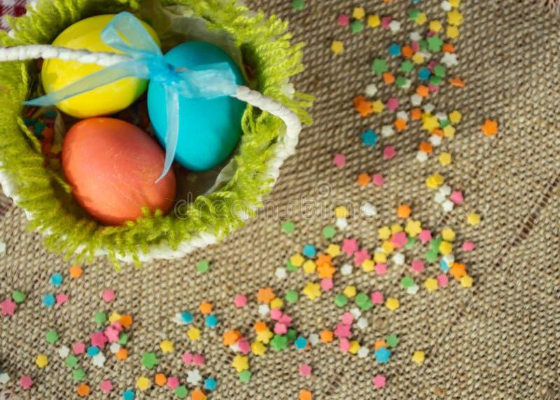 Ovos coloridos na cesta festiva de easter no guardanapo da lona foto de stock