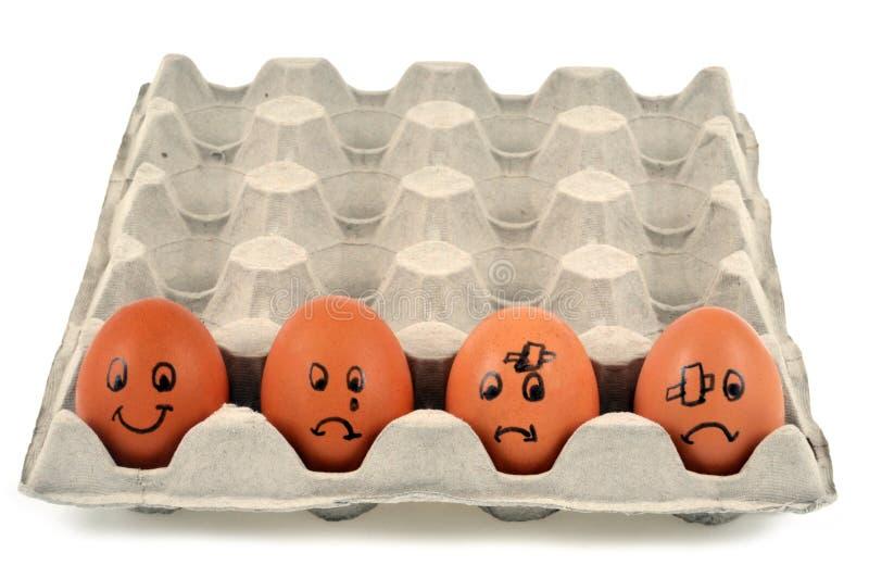Ovos com as caras diferentes tiradas no escudo fotografia de stock