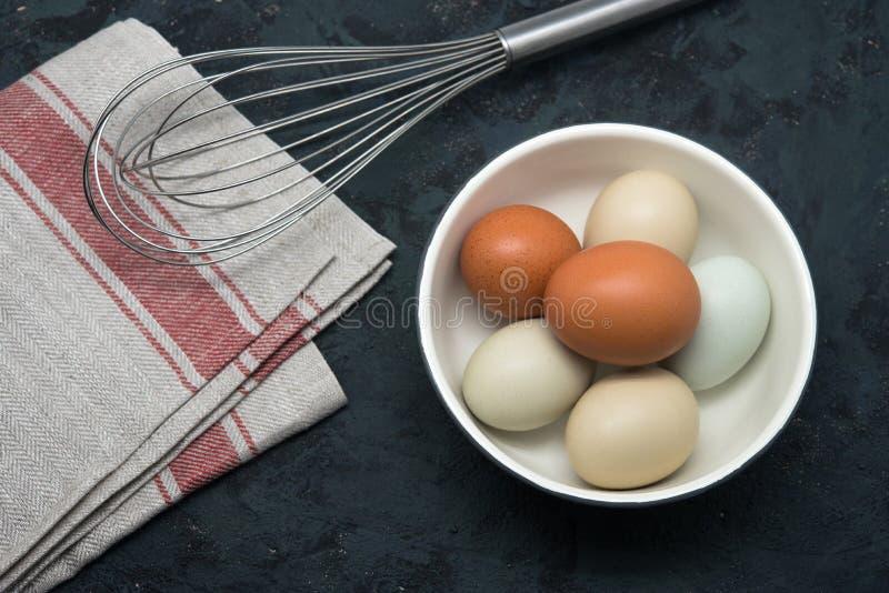 Ovos com o batedor na tabela foto de stock