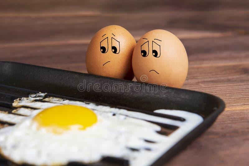 Ovos com uma cara triste perto de um ovo frito imagem c?mico foto de stock