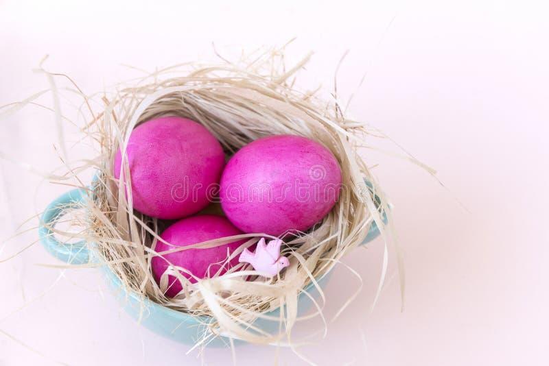 Ovos cor-de-rosa em um ninho em um fundo bege, Páscoa, pombas, placa, vista superior fotografia de stock
