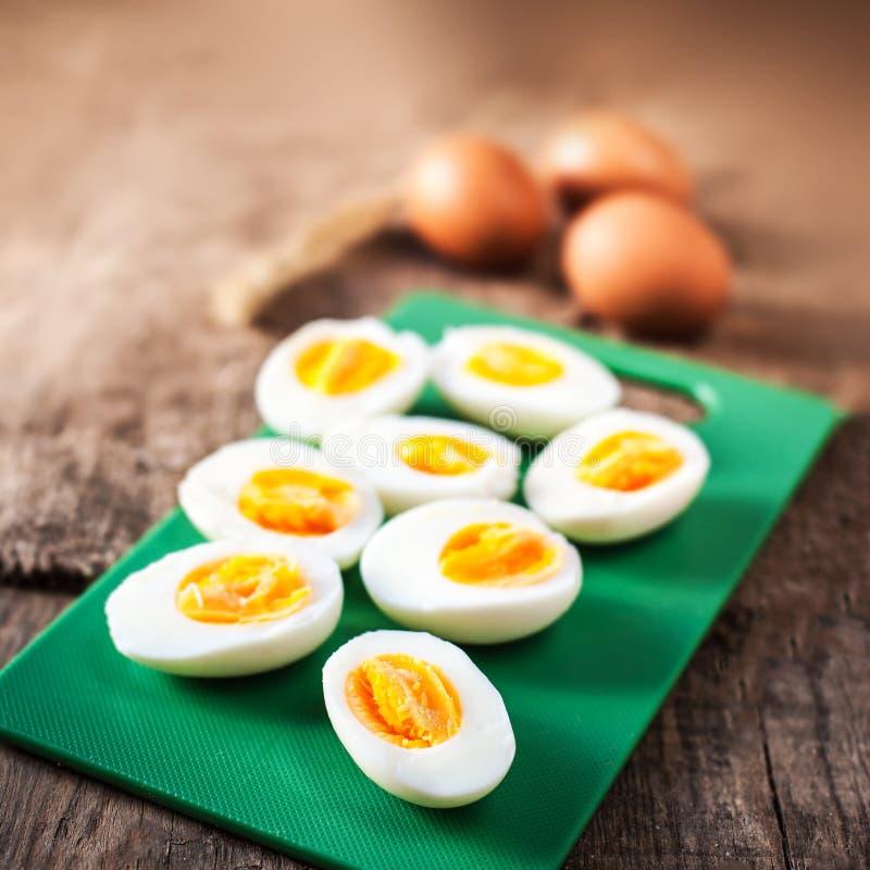 Ovos cozidos duros, cortados ao meio no backg de madeira da placa de corte imagens de stock