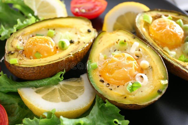 Ovos cozidos no abacate e em legumes frescos na placa, close up foto de stock