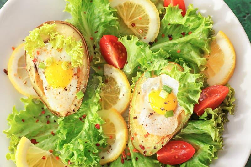 Ovos cozidos no abacate e em legumes frescos na placa, close up imagem de stock