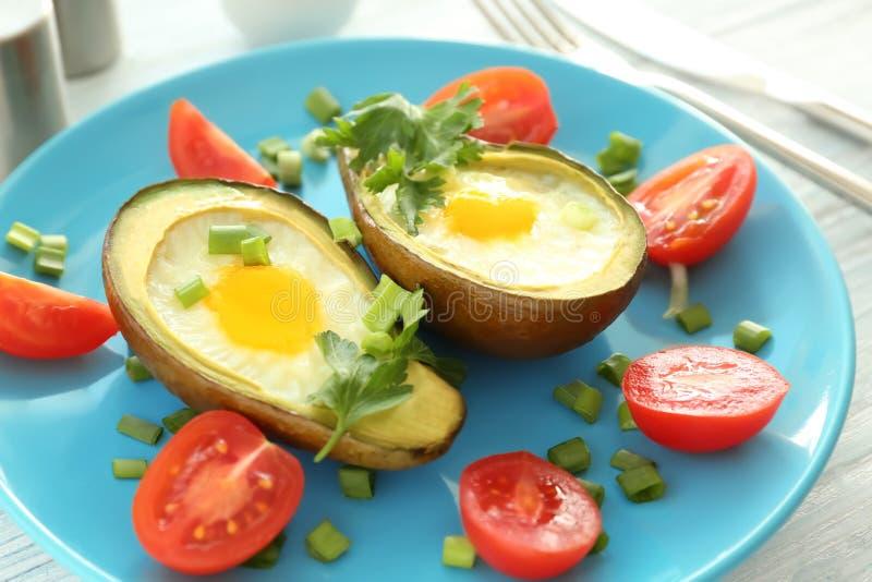 Ovos cozidos no abacate e em tomates frescos na placa, close up fotografia de stock