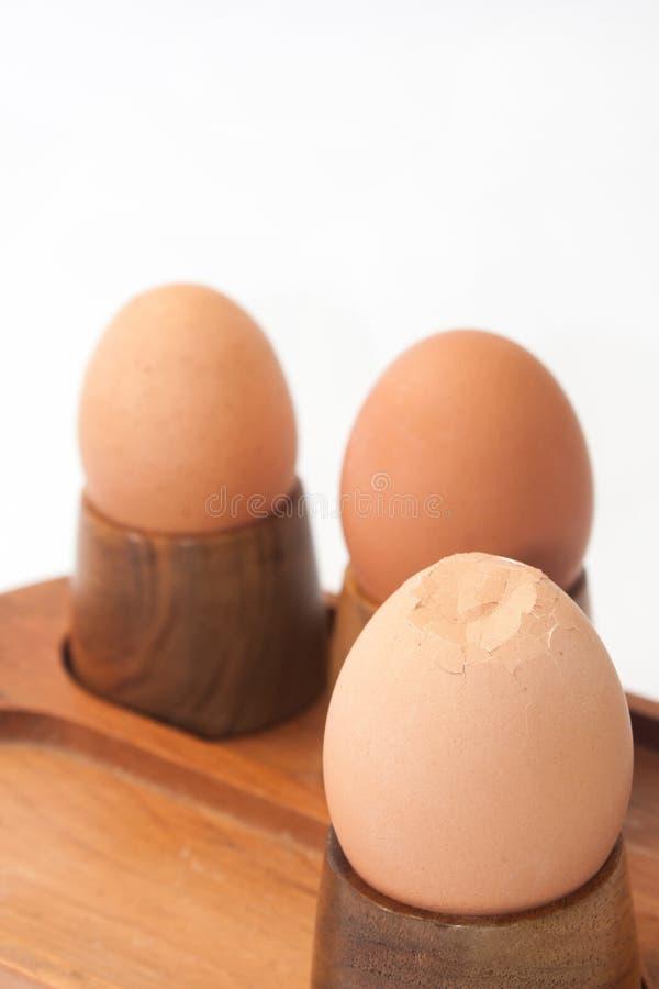 Ovos cozidos no suporte do ovo com ovo rachado imagem de stock