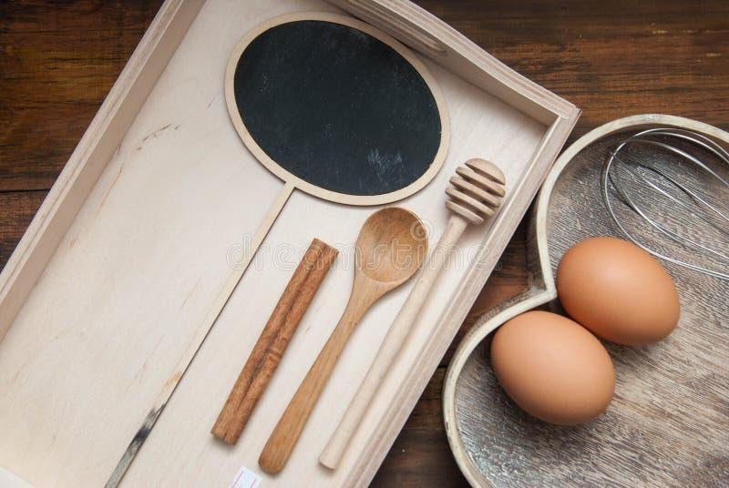 Ovos crus com spooon e as ferramentas de madeira do cozimento Coza ou fundo do alimento O fundo e o coração de madeira rústicos e imagens de stock