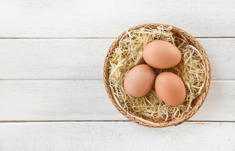 Ovos da galinha no ninho da cesta no fundo de madeira branco foto de stock