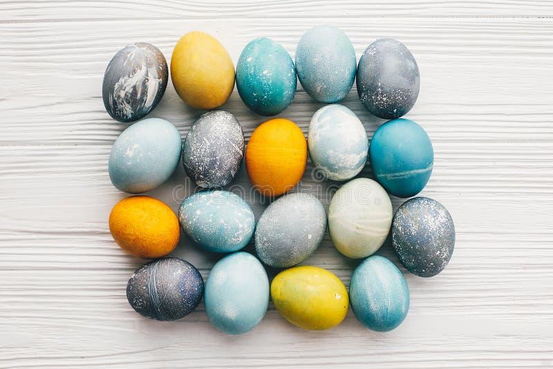 Ovos da páscoa à moda no fundo de madeira branco, configuração lisa Os ovos da páscoa modernos pintaram com a tintura natural no  fotos de stock