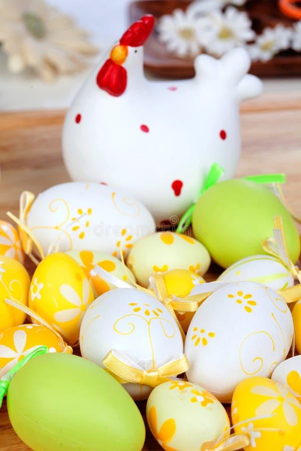 Ovos da páscoa amarelos e verdes com uma galinha cerâmica fotografia de stock royalty free