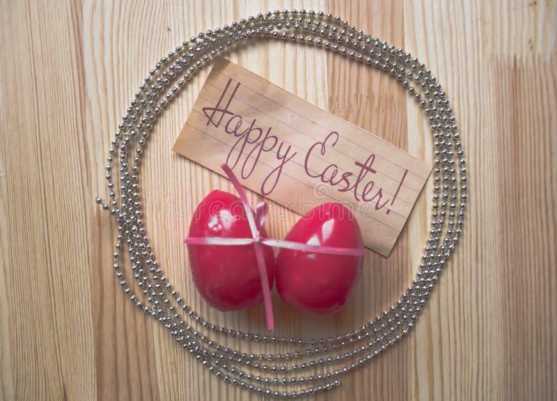 Ovos da páscoa ano novo feliz 2007 A curva cor-de-rosa envolveu ovos e chaplet no fundo de madeira foto de stock