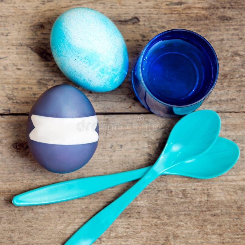 Ovos da páscoa azuis, tinturas do ovo e uma colher na tabela de madeira, copyspace fotos de stock
