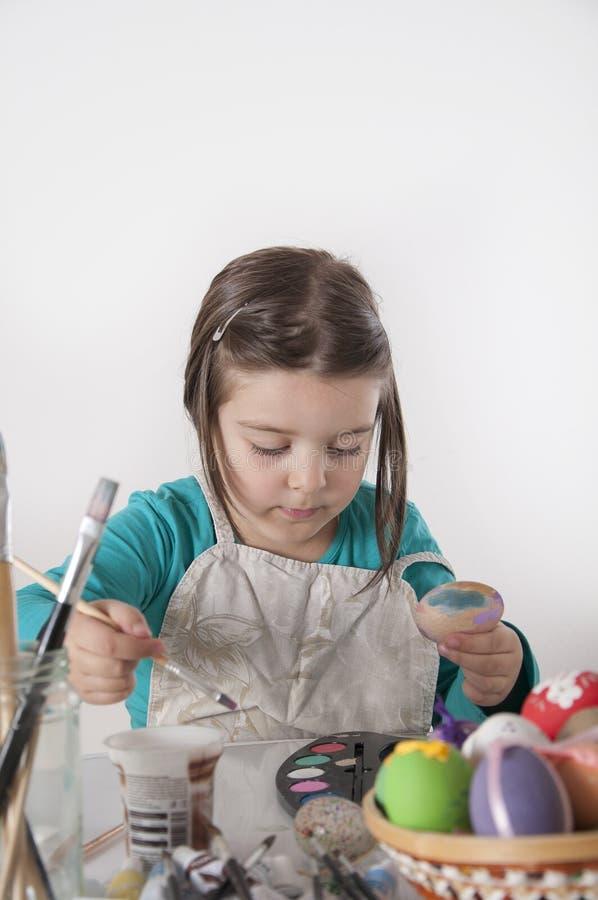 Ovos da páscoa bonitos da pintura da menina imagens de stock