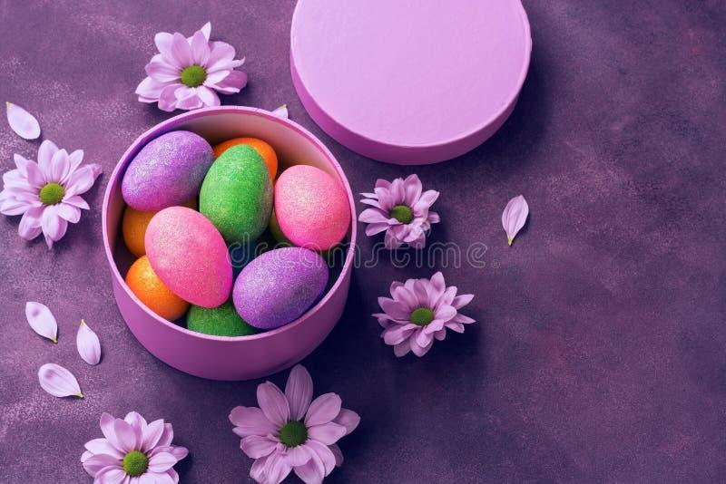 Ovos da páscoa brilhantes coloridos em uma caixa de presente redonda no fundo roxo decorado com flores Vista aérea, espaço da cóp imagens de stock