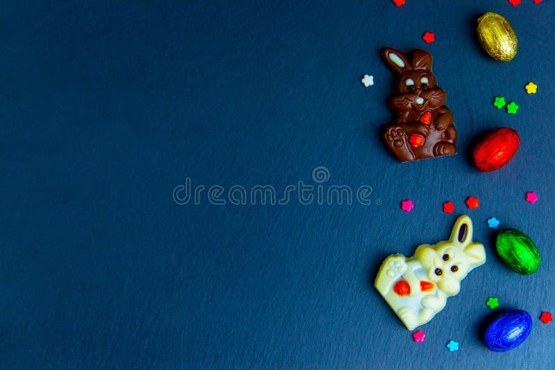 Ovos da páscoa, coelho e doces deliciosos do chocolate em escuro - imagem multicolorido do fundo azul imagem de stock