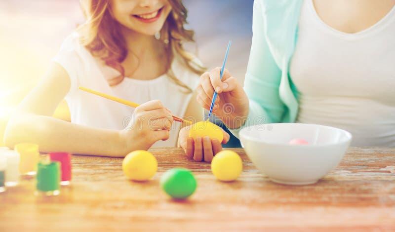 Ovos da páscoa da coloração da filha e da mãe fotos de stock royalty free