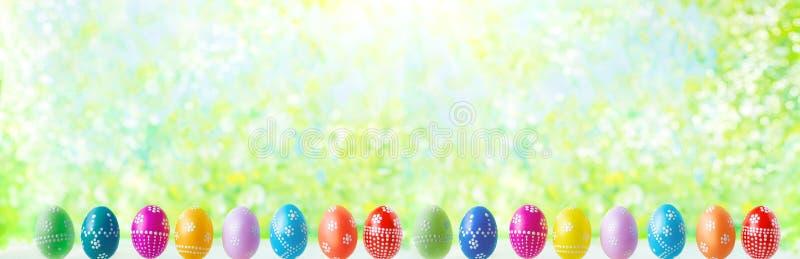 Ovos da páscoa coloridos adiantados brilhantes em um fundo ensolarado da mola imagens de stock
