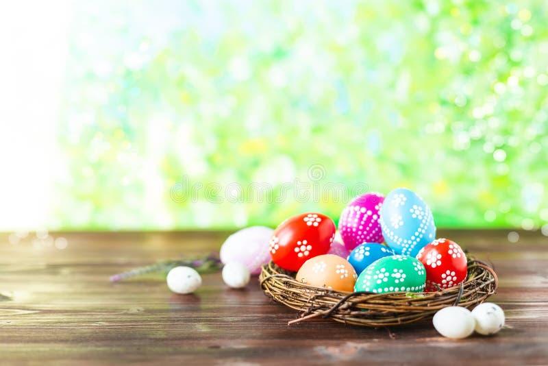 Ovos da páscoa coloridos adiantados brilhantes em um fundo ensolarado da mola imagem de stock