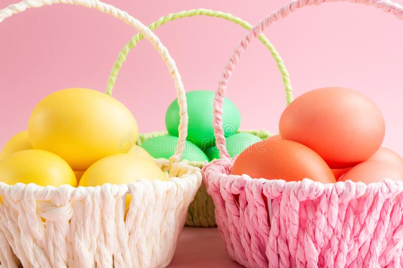 Ovos da páscoa coloridos em cestas coloridas Fundo cor-de-rosa Conceito do feriado da Páscoa imagem de stock