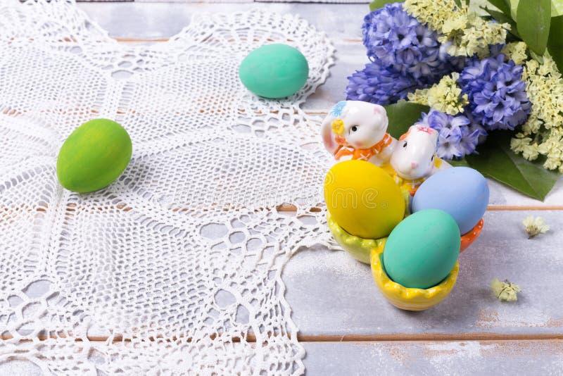 Ovos da páscoa coloridos em um suporte cerâmico do coelho e em um ramalhete da mola com as flores lilás e amarelas em um guardana imagens de stock royalty free